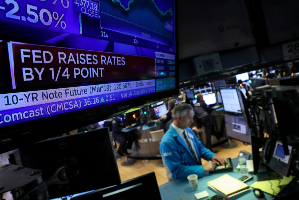 A screen displays the headlines that the U.S. Federal Reserve raised interest rates as a trader works at a post on the floor of the New York Stock Exchange (NYSE) in New York, U.S., December 19, 2018. Photo by REUTERS/Brendan McDermid/File Photo