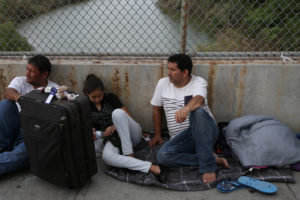 Eduardo (R) and 13-year-old daughter Aura (C), asylum seekers from Guatemala, wait on the Mexican side of the Brownsville-Matamoros International Bridge after being denied entry by U.S. Customs and Border Protection officers near Brownsville, Texas. Photo by Loren Elliott/Reuters