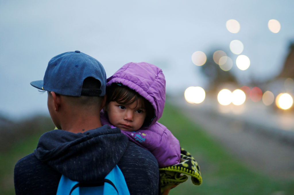 Migrants from Honduras, part of a caravan of thousands from Central America trying to reach the United States, walk near t...