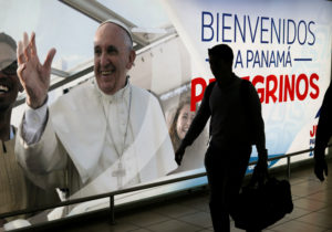 A passenger walks past a poster of Pope Francis at the Tocumen International Airport ahead of Pope Francis' visit for World Youth Day in Panama City, Panama. Photo by Henry Romero/Reuters