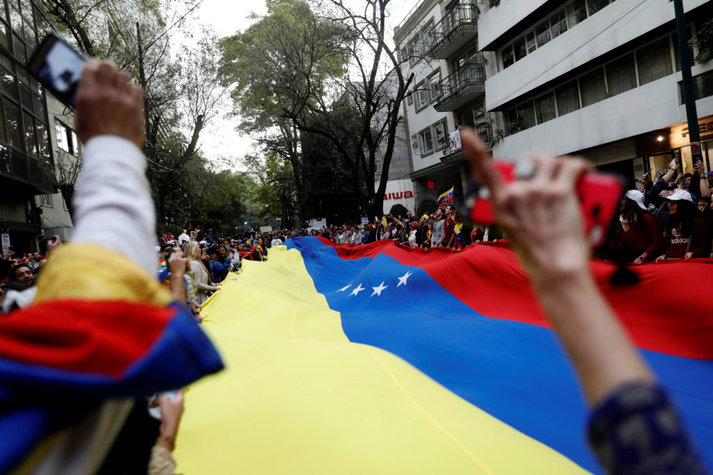 People hold a Venezuelan flag as they gather in support of Venezuela's opposition leader Juan Guaido outside the Embassy o...