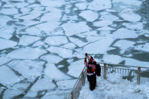A pedestrian stops to take a photo by Chicago River, as bitter cold phenomenon called the polar vortex has descended on much of the central and eastern United States, in Chicago, Illinois. Photo by Pinar Istek/Reuters