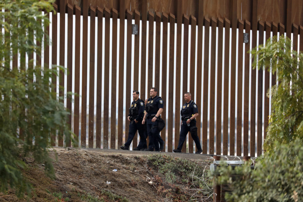 Homeland Security officers walk along the border wall at the San Ysidro border in San Diego, California, U.S., November 29, 2018. REUTERS/Chris Wattie