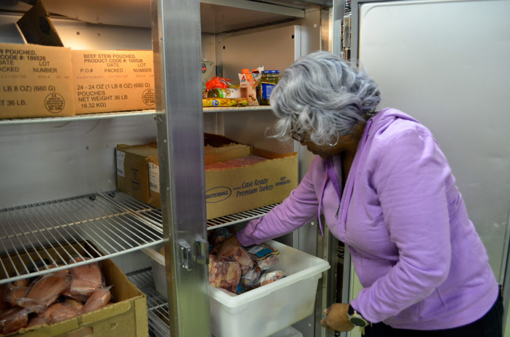 Frazier opens one of the food bank's refrigerators to retrieve packages of chicken and turkey. Recipients can choose between a variety of different cuts of poultry for their monthly food bag. (Photo by Jamie Leventhal)