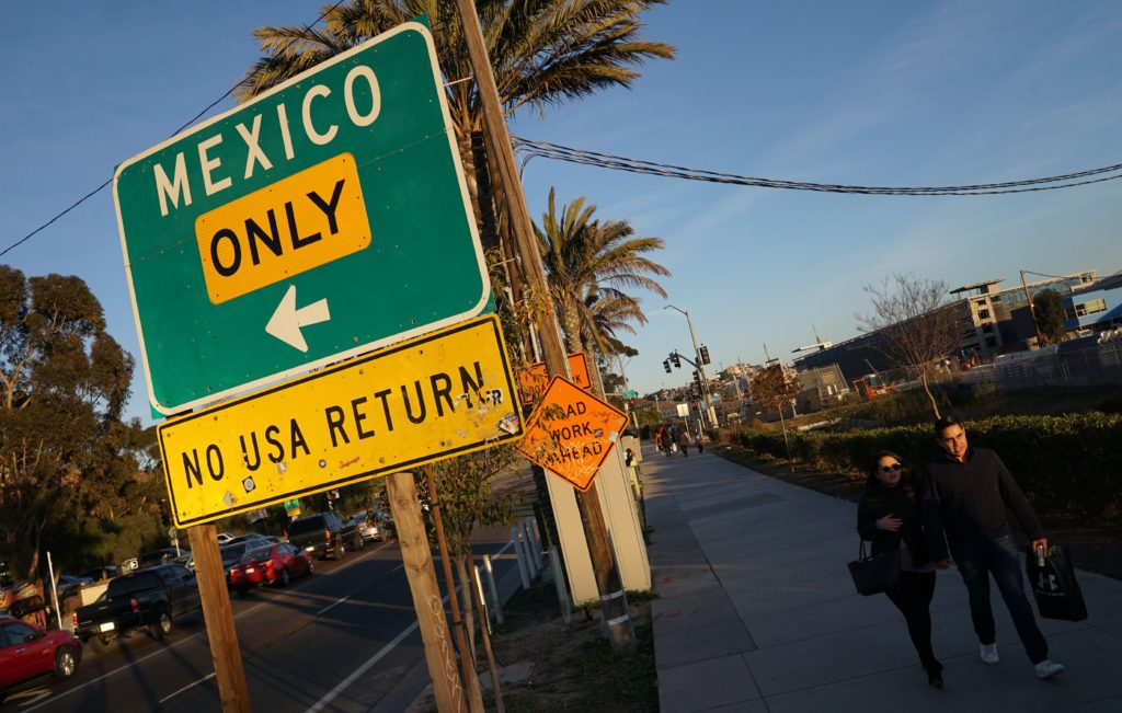 Shoppers walk towards the San Ysidro port of entry after making purchases at outlet malls along along the US-Mexico border in San Ysidro, California. Photo by Sandy Huffaker/AFP/Getty Images