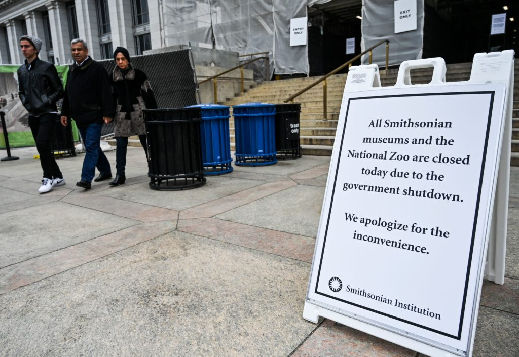 "Tourists walk past a sign posted at the entrance of The National History Museum, stating that all Smithsonian Museums are closed due to the partial shutdown of the US government on January 2, 2019 in Washington, DC. - President Donald Trump warned Wednesday the US federal government may not fully reopen any time soon, as he stood firm on his demand for billions of dollars in funding for a border wall with Mexico. Addressing a cabinet meeting on the 12th day of the partial shutdown, Trump warned it ""could be a long time"" before the impasse is resolved. (Photo by Andrew Caballero-Reynolds / AFP) (Photo credit should read ANDREW CABALLERO-REYNOLDS/AFP/Getty Images)"