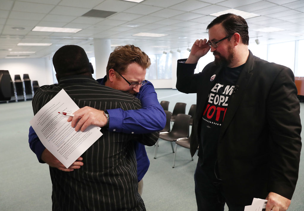 Lance Wissinger is hugged by Permon Thomas as Neil Volz looks on (R) as they fill out their voter registration forms at the Lee County Supervisor of Elections office on January 08, 2019 in Fort Myers, Florida. Mr. Wissinger and Mr. Volz, both with felony records, are now able to register to vote for the first time after a new constitutional amendment took effect, which automatically restores voting rights to most people who have felonies on their record. Photo by Joe Raedle/Getty Images