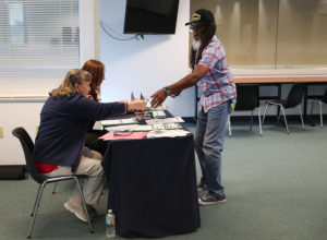Clarence Singleton registers to vote with Rosey Brockamp (L) and Sheryl Podley, who are voter registration workers, at the Lee Country Supervisor of Elections office in Fort Myers, Florida. Photo by Joe Raedle/Getty Images