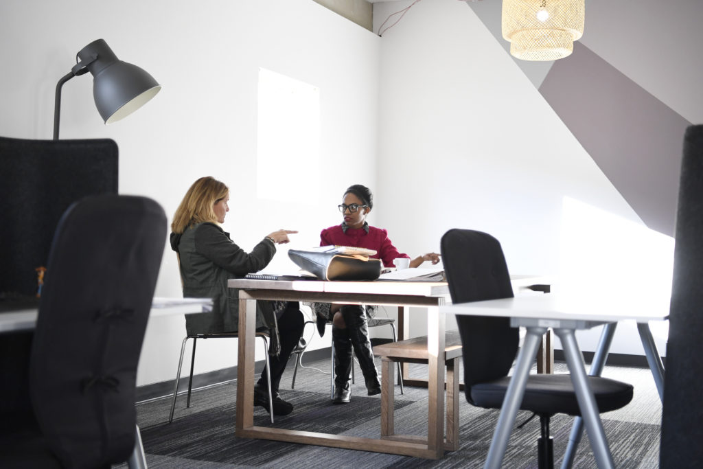 Two women sit at a workspace at Women in Kind. Women in Kind is a co-working space rented out by various small businesses and individuals. Though the space is occupied mostly by women, some men do utilize it. Photo by AAron Ontiveroz/The Denver Post via Getty Images