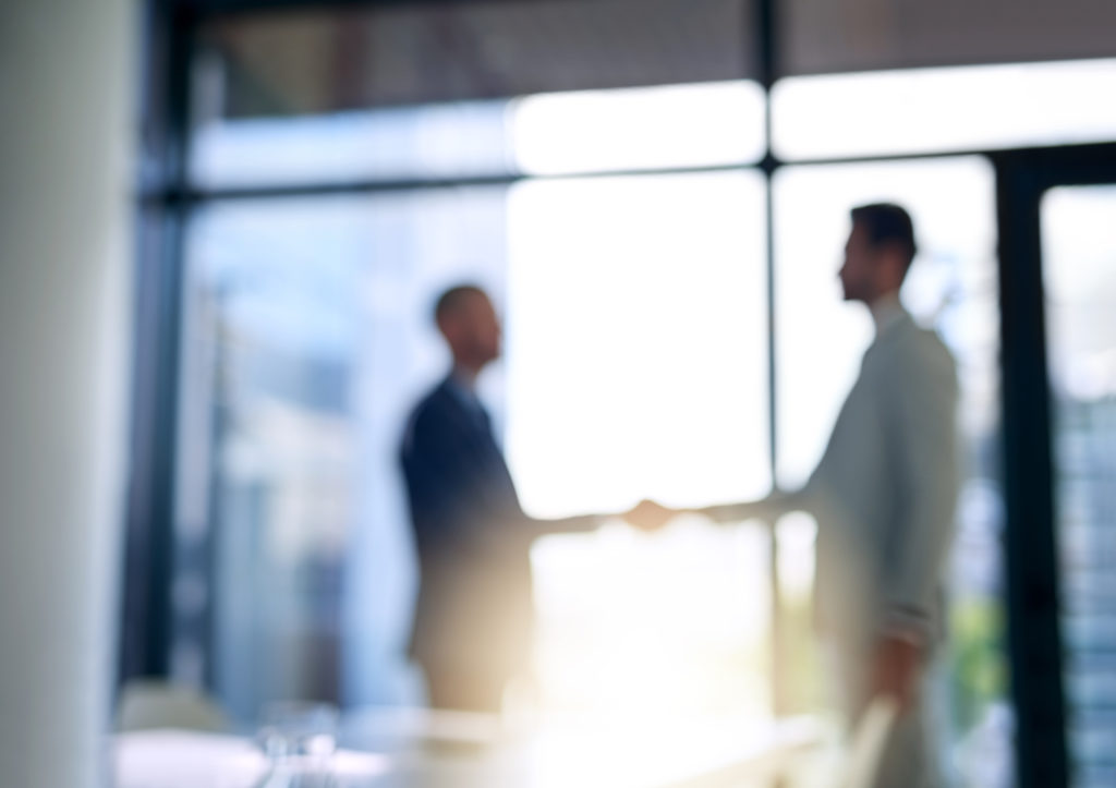 Blurred shot of two businessmen shaking hands in a modern office