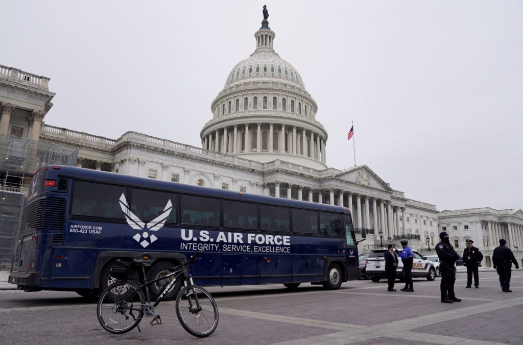 A U.S. Air Force bus meant to transport U.S. Speaker of the House Nancy Pelosi and other members of a congressional delegation to a flight to Belgium and Afghanistan sits guarded by U.S. Capitol Police in front of the Capitol after President Donald Trump cancelled the Air Force flight as the president's dispute with congressional Democrats over the partial government shutdown continues in Washington, U.S., January 17, 2019. REUTERS/Joshua Roberts