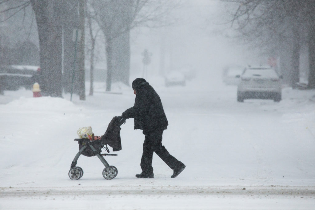 A man pushes a stroller with groceries as flurries swirl around on Woodward Ave. in Detroit, Michigan. Photo by Ryan Garza/Detroit Free Press/TNS via Getty Images