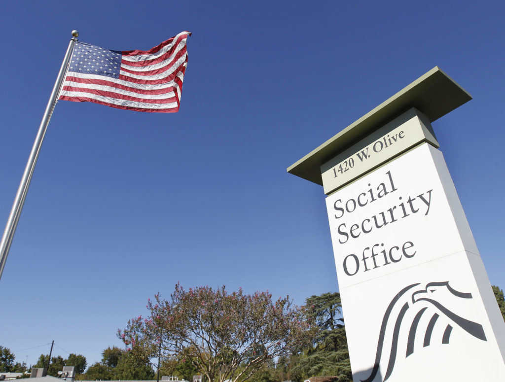 An American flag flutters in the wind next to signage for a United States Social Security Administration office in Burbank, California. Photo by Fred Prouser/Reuters