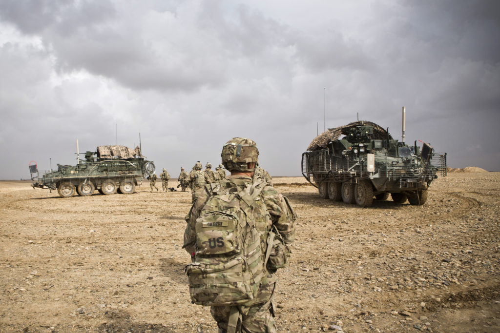 U.S. Army soldiers with Charlie Company, 36th Infantry Regiment, 1st Armored Division head back to their vehicles at the e...