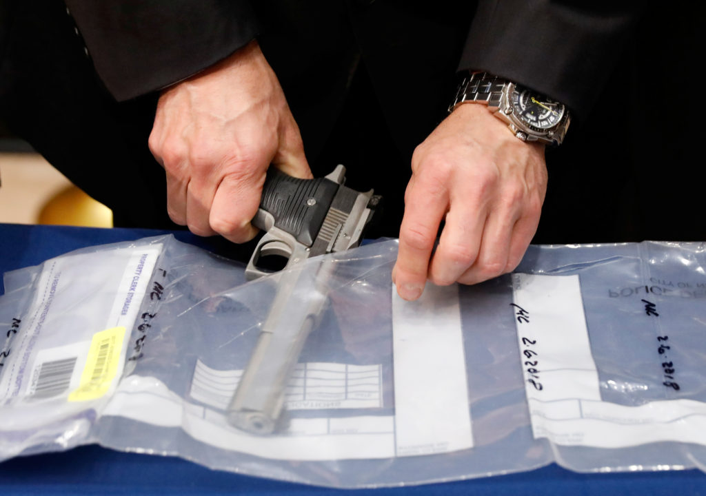 A confiscated handgun is placed into an evidence bag during a news …
