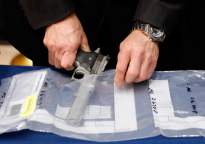 A confiscated handgun is placed into an evidence bag during a news conference about a gun bust at New York City Police Headquarters in New York. Photo by Brendan McDermid/Reuters