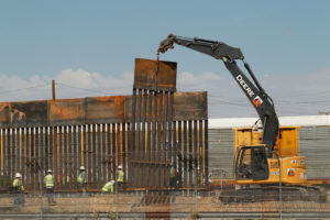 U.S. workers are seen next to heavy machinery while working on a new bollard wall in El Paso, Texas, as seen from the Mexican side of the border in Ciudad Juarez. Photo by Jose Luis Gonzalez/Reuters