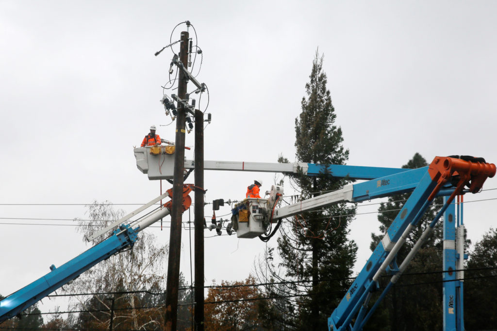 PG&E crew work on power lines to repair damage caused by the Camp Fire in Paradise, California, on November 21, 2018. Photo by Elijah Nouvelage/Reuters