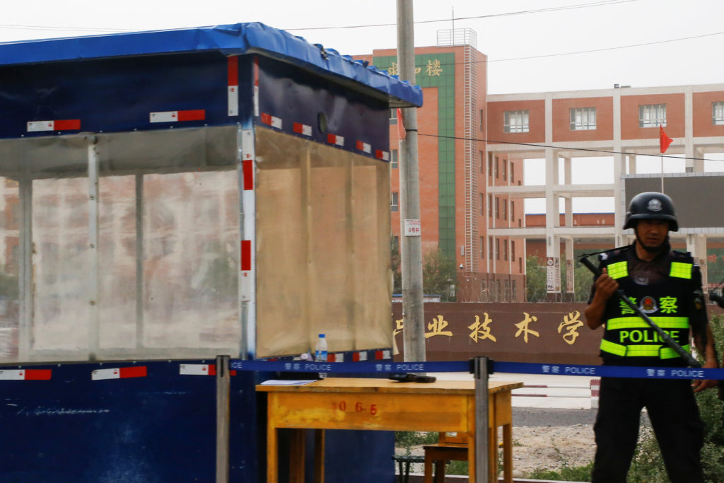 An armed police officer stands guard outside the entrance of what is officially called a vocational skills education centre in Hotan in Xinjiang Uighur Autonomous Region, China. Picture taken September 7, 2018. Thomas Peter/Reuters