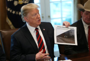 "President Donald Trump holds up a photo of a ""Typical Standard Wall Design"" as he hosts a ""roundtable discussion on border security and safe communities"" with state, local, and community leaders in the Cabinet Room of the White House in Washington, D.C. Photo by Leah Millis/Reuters"