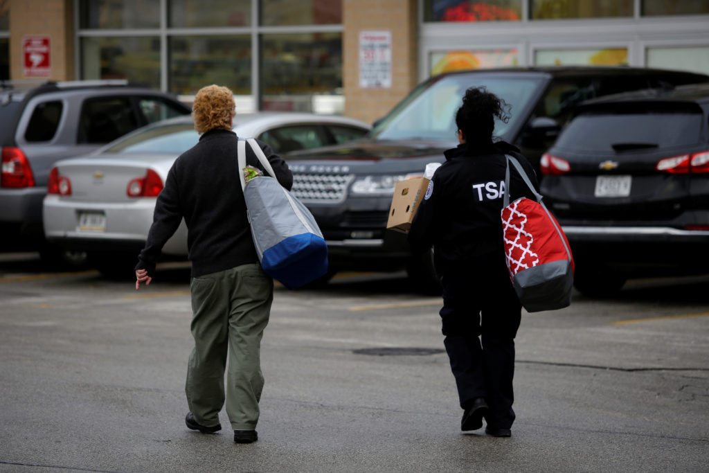 A TSA worker walks to her vehicle after receiving food from the Lakeview Pantry in Chicago on January 14, 2019. Joshua Lott/Reuters