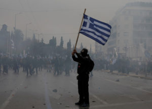 A protester holds a Greek national flag as he takes a part in a demonstration against the agreement reached by Greece and Macedonia to resolve a dispute over the former Yugoslav republic's name, in Athens, Greece on January 20, 2019. Photo by Alkis Konstantinidis/Reuters