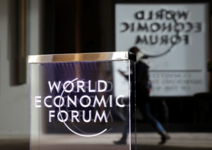 A person passes by a World Economic Forum logo in Davos, Switzerland. The International Monetary Fund announced in Davos on Monday that it was cutting its forecast for 2019 economic growth. Photo by Arnd Wiegmann/Reuters