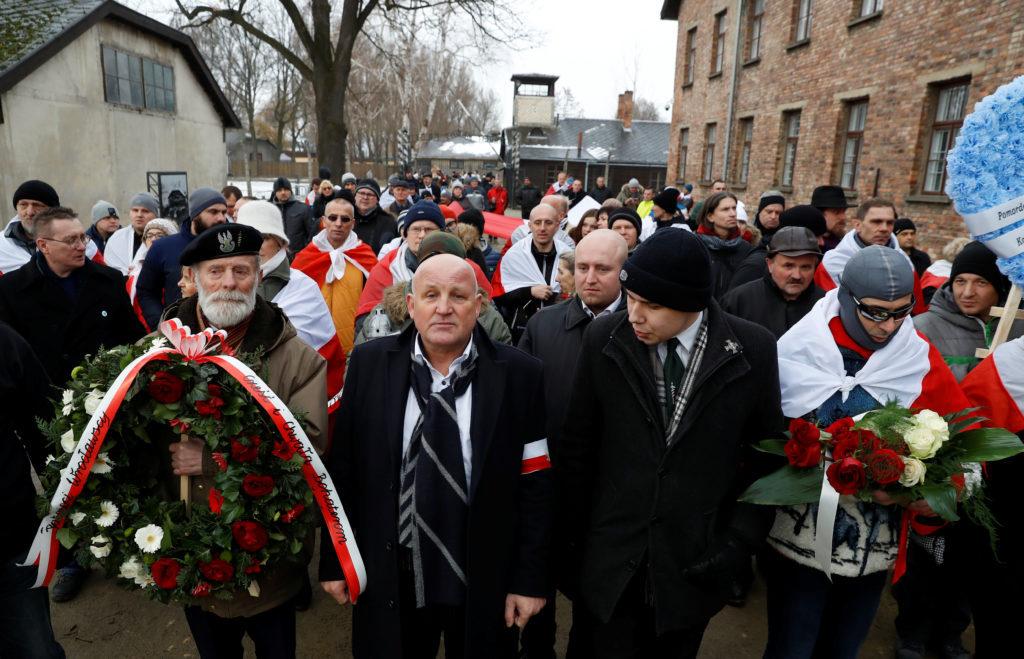 "Far right activists walk past the ""Arbeit Macht Frei"" gate at the former Nazi German concentration and extermination camp Auschwitz, to pay tribute to Polish victims at the ""death wall"", during the ceremonies marking the 74th anniversary of the liberation of the camp and International Holocaust Victims Remembrance Day, in Oswiecim, Poland, January 27, 2019. Photo by Kacper Pempel/Reuters"