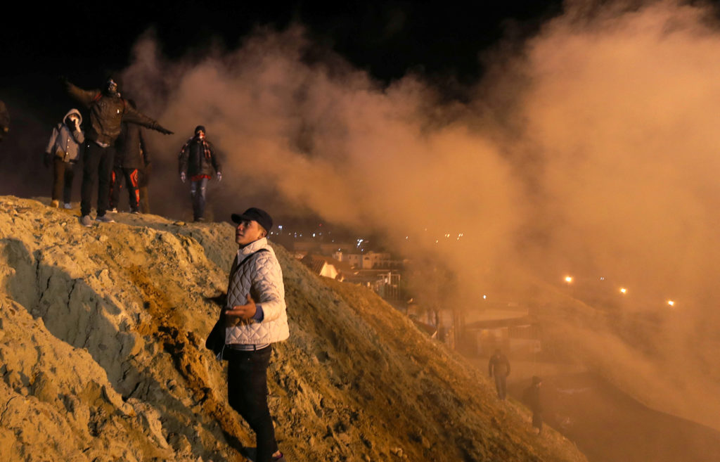 Migrants, part of a caravan of thousands from Central America trying to reach the United States, react after U.S. Customs and Border Protection (CBP) throw tear gas to the Mexican side of the fence as they prepared to cross it illegally, in Tijuana, Mexico, January 1, 2019. REUTERS/Mohammed Salem - RC17C4EC1140