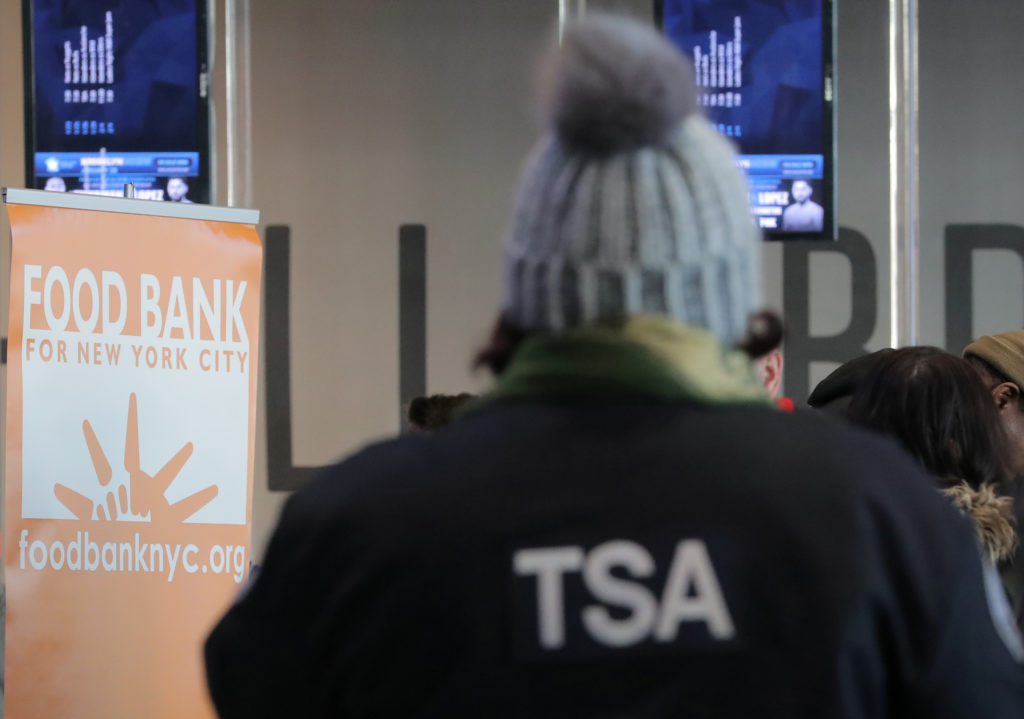 A Transportation Security Administration (TSA) employee receives a donation at a food distribution center for federal work...