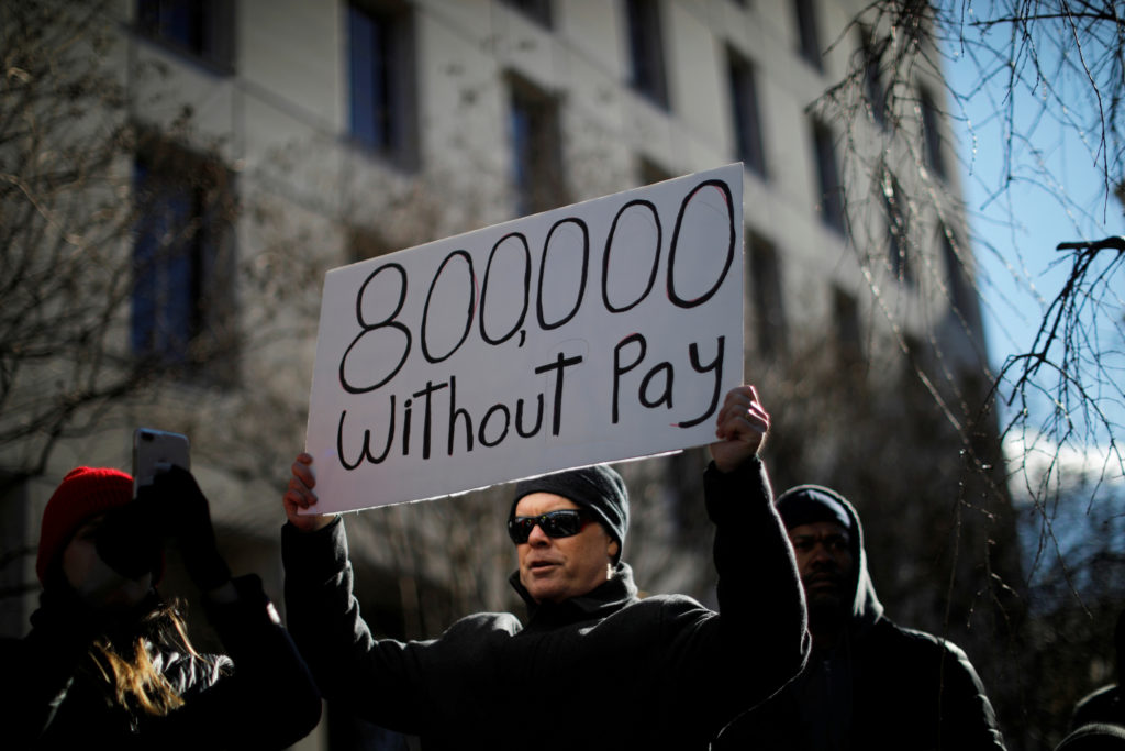 FILE PHOTO: A demonstrator holds a sign, signifying hundreds of thousands of federal employees who won't be receiving thei...