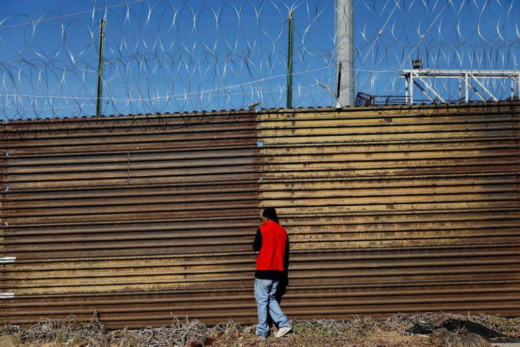A migrant, part of a caravan of thousands traveling from Central America en route to the United States, looks at U.S. border patrol officers through holes in the border wall between the U.S. and Mexico in Tijuana, Mexico Nov. 25, 2018. Photo by REUTERS/Edgard Garrido