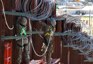 Soldiers from the 87th Sapper Company, 20th Engineer Battalion, 36th Engineer Brigade, string concertina wire and barbed wire along the top of the border fence at the DeConcini Port of Entry in Nogales, Arizona. Photo by U.S. Army/Sgt. Kyle Larsen/Handout via Reuters