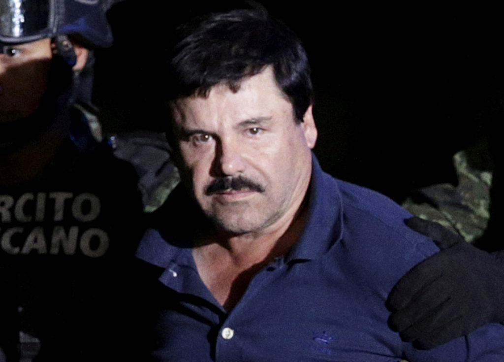 """Recaptured drug lord Joaquin """"El Chapo"""" Guzman is escorted by soldiers at the hangar belonging to the office of the Attorn..."""