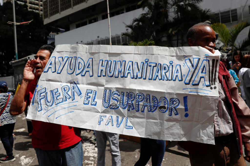 """Supporters of Venezuelan opposition leader and self-proclaimed interim president Juan Guaido hold a banner reading """"humanitarian aid now outside the usurper"""" during a protest against Venezuelan President Nicolas Maduro's government in Caracas, Venezuela January 30, 2019. Photo by Carlos Garcia Rawlins/Reuters"""