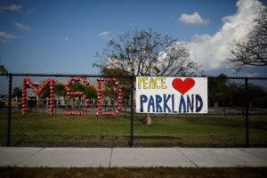 The initials of Marjory Stoneman Douglas High School and a placard are placed on the fence at Park Trails Elementary School, following a mass shooting in Parkland, Florida. Photo by Carlos Garcia Rawlin/Reuters