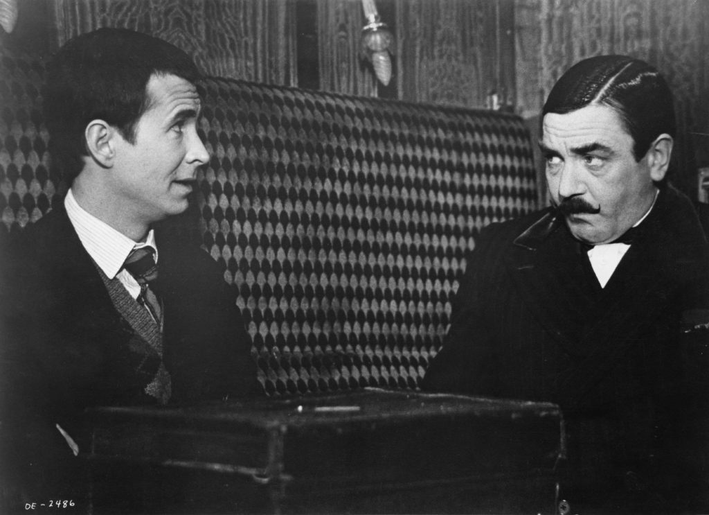 Actors Anthony Perkins (left), and Albert Finney (as Hercule Poirot) in a scene from Agatha Christie's 'Murder On The Orient Express', 1974. Photo by EMI Films/Archive Photos/Getty Images