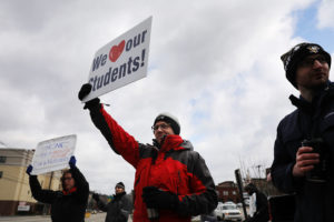 MORGANTOWN, WV - MARCH 02: West Virginia teachers, students and supporters hold signs on a Morgantown street as they continue their strike on March 2, 2018 in Morgantown, West Virginia. Despite a tentative deal reached Tuesday with the state's governor, teachers across West Virginia continued to strike on Friday as the Republican-controlled state legislature debated the governor's deal. (Photo by Spencer Platt/Getty Images)