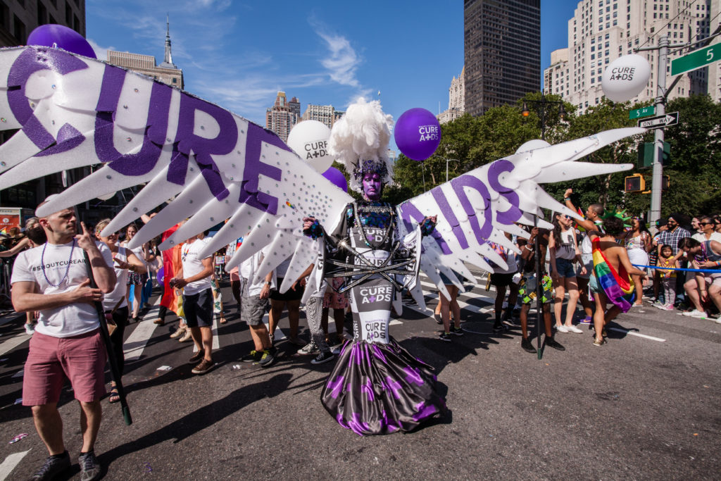 New York City Heritage of Pride March filled Fifth Avenue for hours with groups from the LGBT community and it's supporters. Marchers from the Research Foundation to Cure Aids are lead by a tall man in purple facepaint and with white wings that span two lanes of the street. (Photo by: Ed Lefkowicz /VW Pics/UIG via Getty Images)