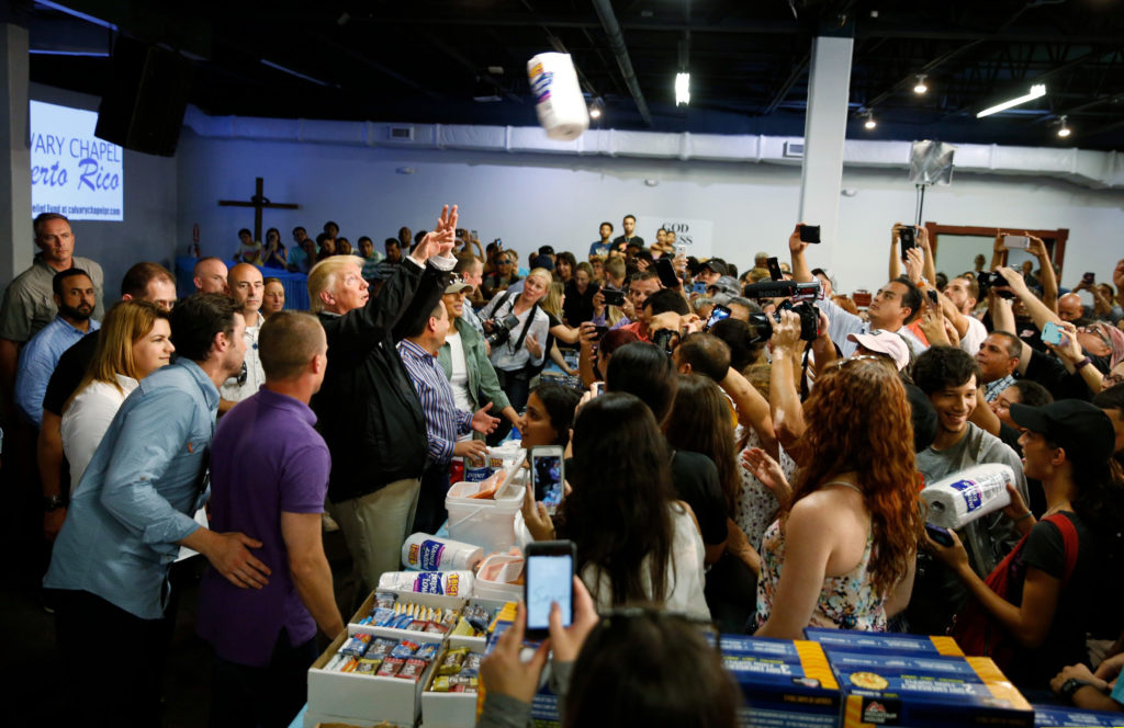 U.S. President Donald Trump throws rolls of paper towels into a crowd of local residents affected by Hurricane Maria as he visits Calgary Chapel in San Juan, Puerto Rico, U.S., October 3, 2017. REUTERS/Jonathan Ernst - HP1EDA31DNU0E