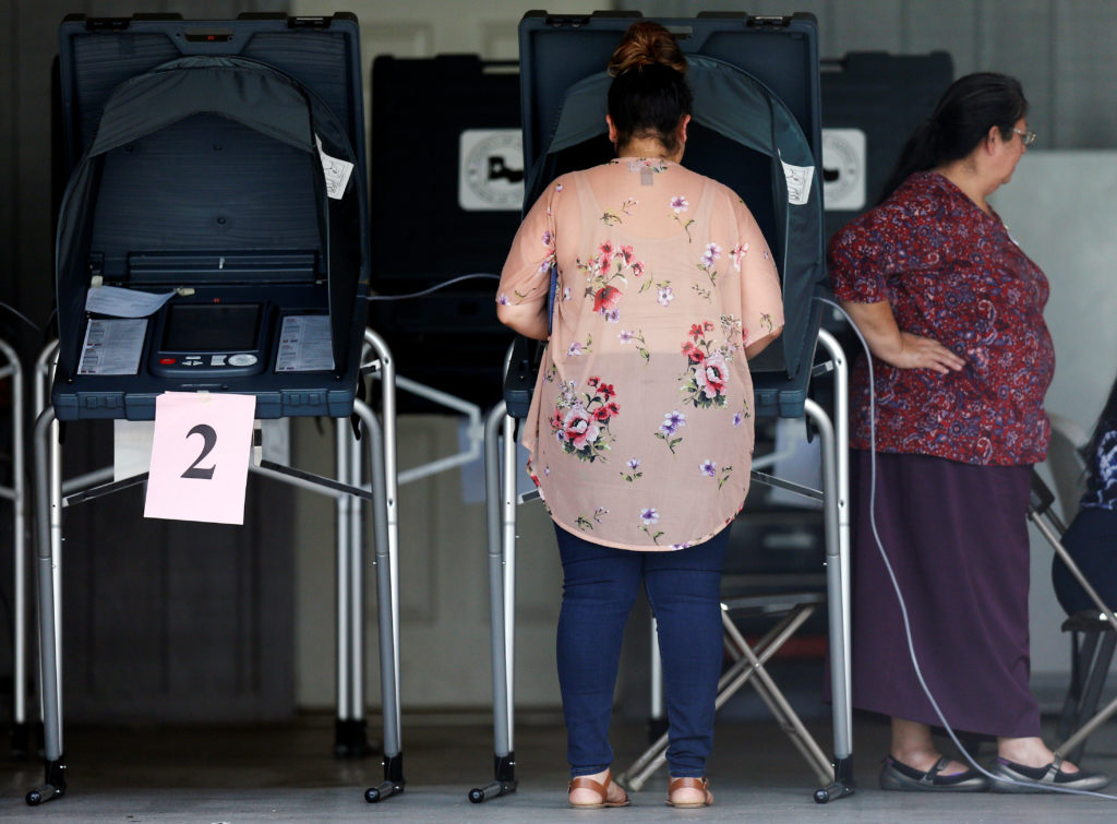 A woman votes at a polling station during the midterm elections in …