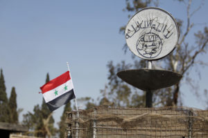 A Syrian national flag flutters next to the Islamic State's slogan at a roundabout where executions were carried out by ISIS militants in the city of Palmyra, in Homs Governorate, Syria in this April 1, 2016 file photo. Omar Sanadiki/Reuters