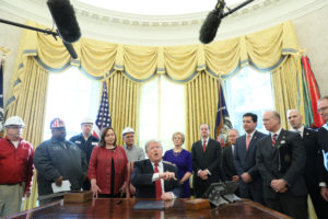 President Donald Trump signs an Executive Order at a meeting with manufacturers and manufacturing workers in the Oval Office of the White House on January 31, 2019. Photo by Jonathan Ernst/Reuters