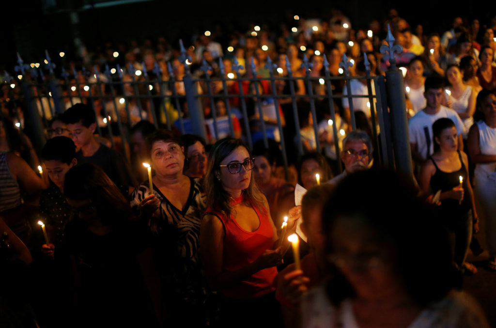 Relative and friends of victims of a collapsed tailings dam owned by Brazilian mining company Vale SA, carry candles as they pay respects during a vigil in Brumadinho, Brazil January 31, 2019. Photo by Adriano Machado/Reuters