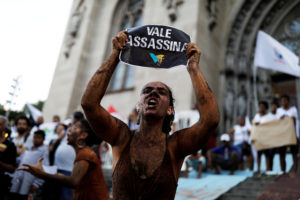 "An activist covered in mud, holds a sign reading "" VALE SA, Killer !"" during a protest against the Brazilian mining company Vale SA, in front of the Se Cathedral in Sao Paulo, Brazil, February 1, 2019. Photo by Nacho Doce/Reuters"