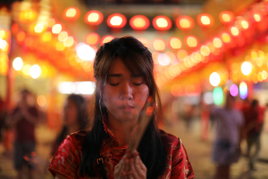 A woman lights incense while praying in a Chinese temple during the celebration of the Lunar New Year in Chinatown in Bangkok, Thailand on February 4, 2019. Photo by Jorge Silva/Reuters