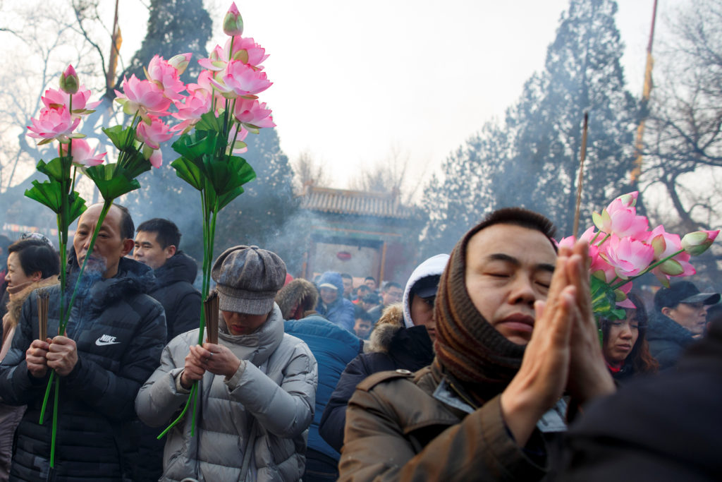 People burn incense sticks and pray for good fortune at Yonghegong Lama Temple on the first day of the Lunar New Year of the Pig in Beijing. Photo by Thomas Peter/Reuters