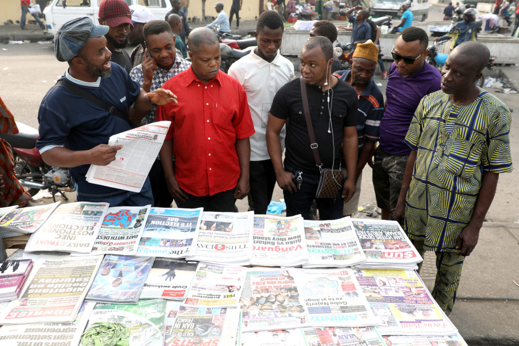 People read newspapers after the postponement of the presidential election in Lagos, Nigeria February 16, 2019. Photo by Temilade Adelaja/Reuters