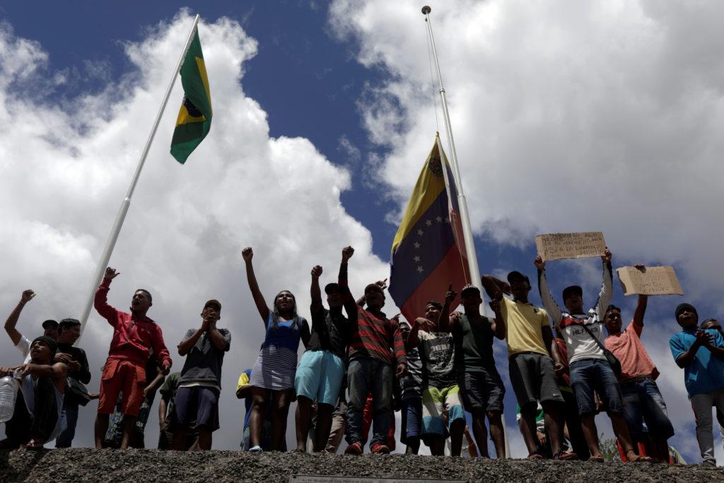 People waiting to cross to Venezuela gesture at the border between …