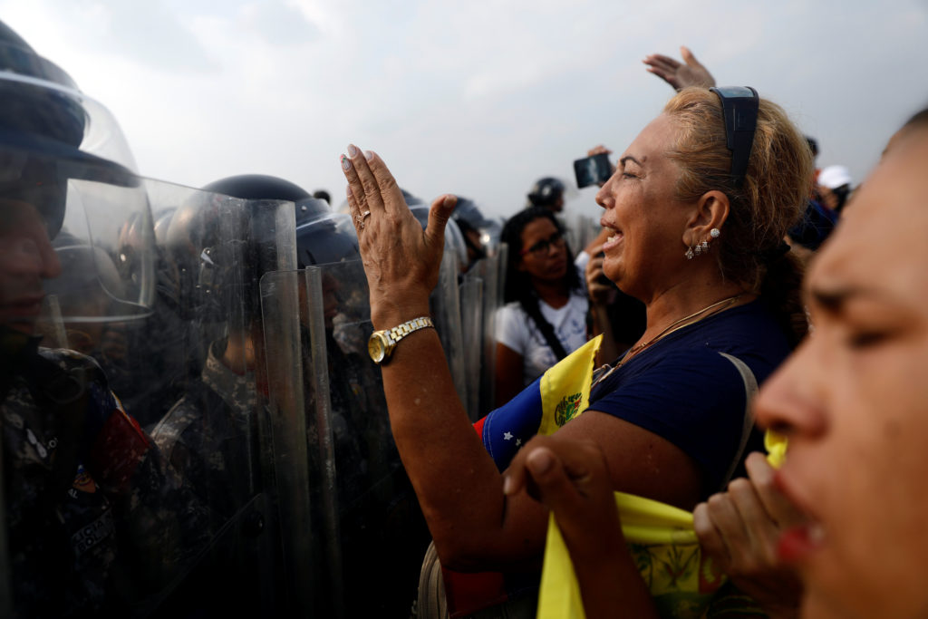 Venezuela's opposition supporters demand to cross the border line between Colombia and Venezuela at Simon Bolivar bridge as Venezuela's security forces stand in the border line blocking their way in the outskirts of Cucuta, Colombia, February 23, 2019. REUTERS/Edgard Garrido - RC1FDBCBE640